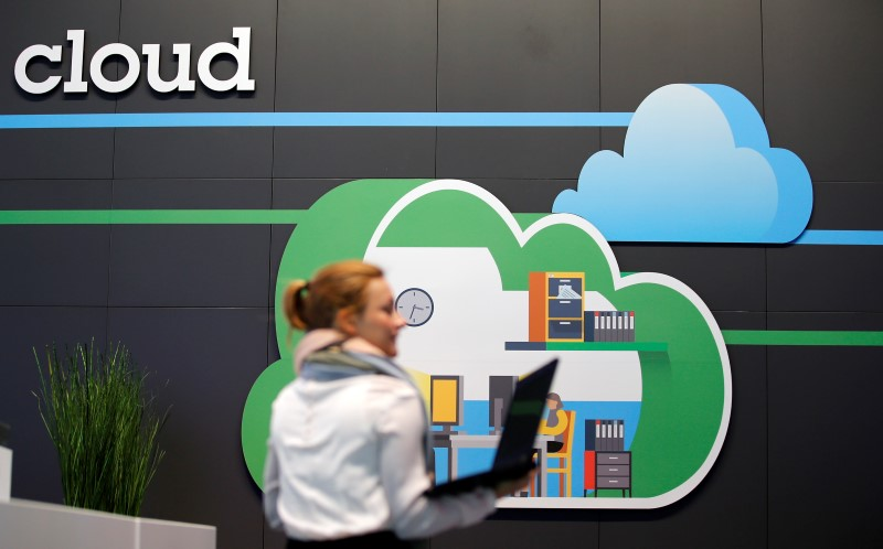 A women holds her laptop as she walks in front of a cloud computing logo at the booth of IBM during preparations for the CeBIT trade fair in Hanover, March 9, 2014. REUTERS/Fabrizio Bensch