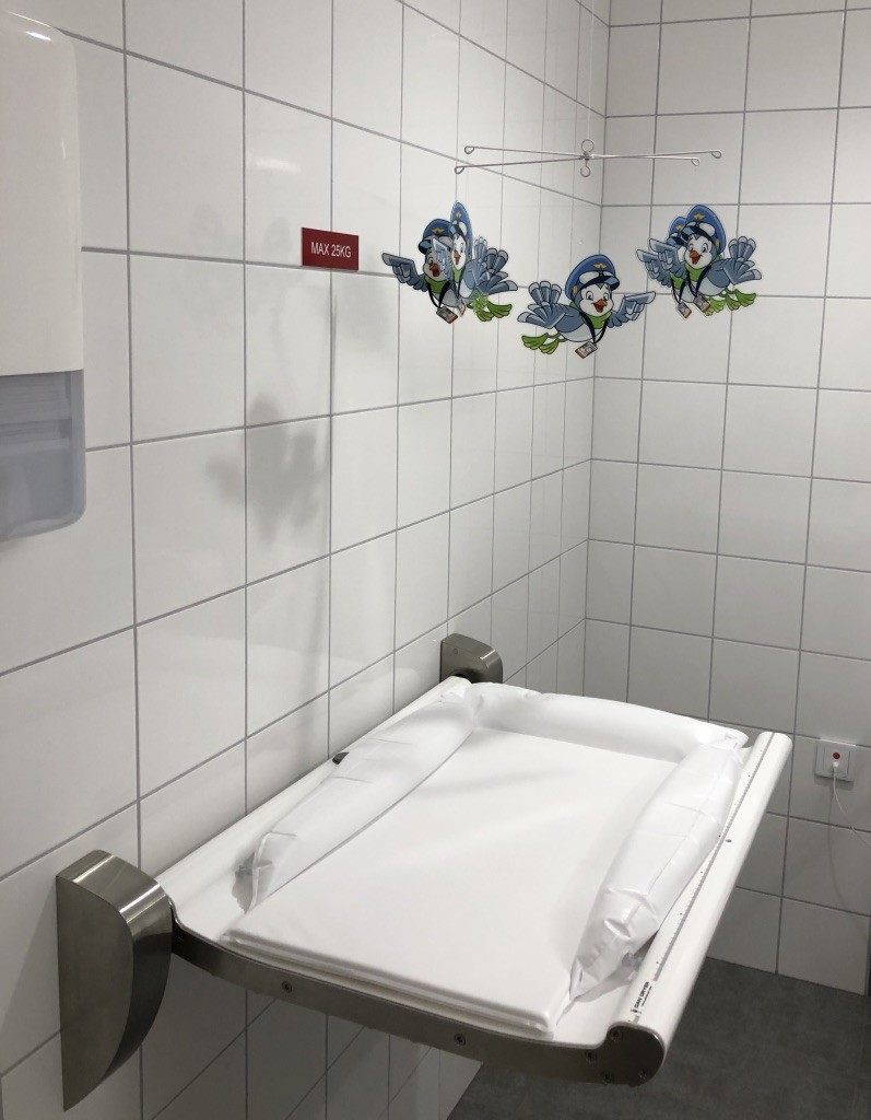 A photo of a diaper changing station at an airport in Sweden.